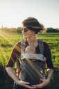 Mother carrying son in baby stroller while standing on grassy field against clear sky - CAVF52470