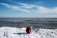 Side view of girl playing with snow while crouching by sea against sky during winter - CAVF52494