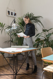 Businesswoman examining file while standing at desk in office - CAVF52509