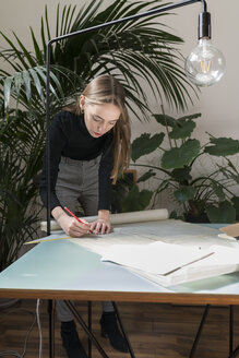 Businesswoman drawing blueprints while standing in office - CAVF52512