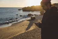 Smiling man using mobile phone while standing at beach against sky during sunset - CAVF52530