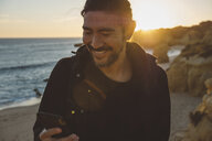 Smiling man using smart phone while standing at beach during sunset - CAVF52533