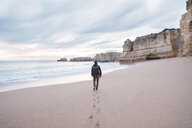 Rear view of man with backpack walking at beach against cloudy sky during sunset - CAVF52545