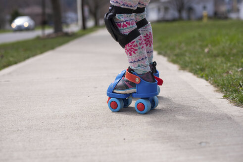 Low section of girl roller skating on footpath at park - CAVF52563