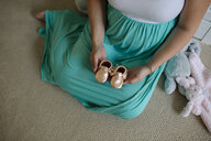 Low section of pregnant woman holding baby booties while sitting on carpet at home - CAVF52605