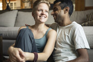 Smiling young couple sitting in living room at home - TGBF01150