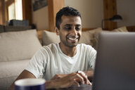 Smiling mid adult man using laptop in living room at home - TGBF01156