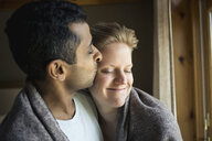 Romantic couple wrapped in blanket kissing at home - TGBF01159