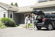 Full length of mid adult couple unloading groceries from car outside house - TGBF01165
