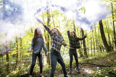Happy boy and girls playing with colorful flares while jumping in forest - TGBF01195