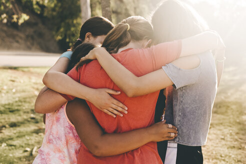 Girls forming huddle in park on sunny day - TGBF01210