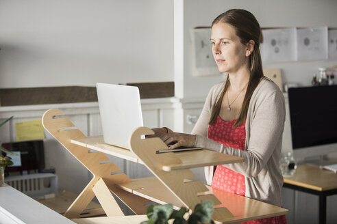 Businesswoman surfing internet on laptop in creative office - TGBF01306