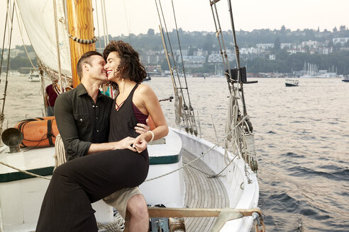 Smiling man and woman embracing while sitting on boat against sky during sunset - TGBF01462