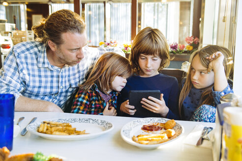 Angry daughter looking at father by siblings using digital tablet at table in restaurant - TGBF01534