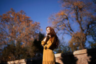 A woman standing by trees under a clear blue sky in the autumn - INGF05512