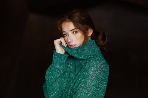 Studio shot of a redheaded woman with freckles and a green sweater - INGF05515