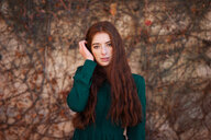 Portrait of a young redheaded woman standing in the forest during autumn - INGF05518