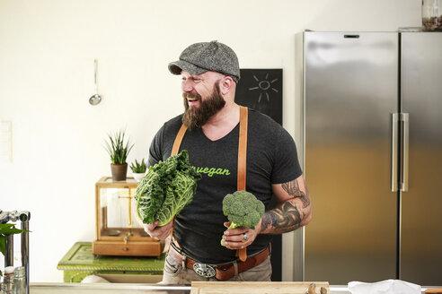 Vegan man choosing vegetables in his kitchen - REAF00347