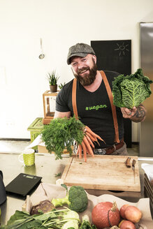 Vegan man choosing vegetables in his kitchen - REAF00350