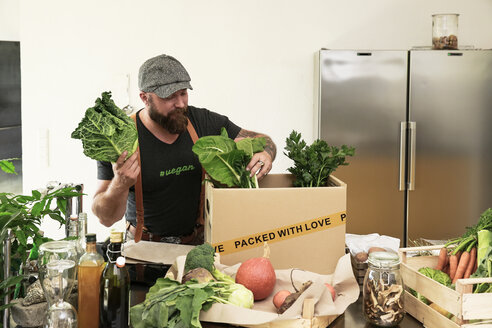 Mature man with delivery service packing organic vegetables in cardboard - REAF00362