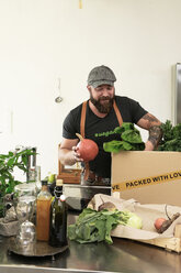 Mature man with delivery service packing organic vegetables in cardboard - REAF00365
