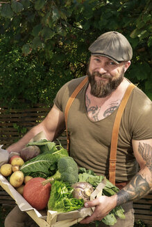 Mature man carrying crate with vegetables in his garden - REAF00386