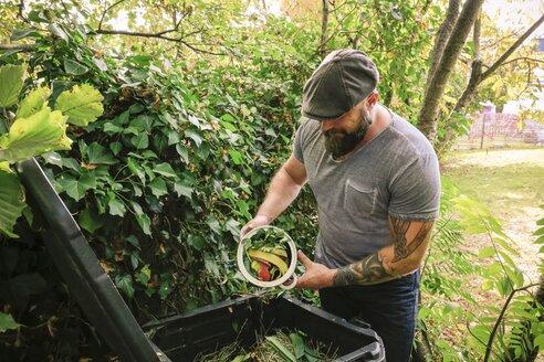 Mature man discarding kitchen scraps on compost pile - REAF00392