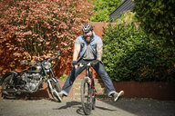 Portrait of happy man switching from motorbike to bicycle - REAF00398