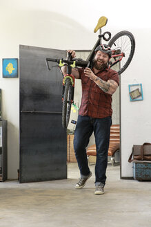 Portrait of laughing man carrying bicycle in office - REAF00407
