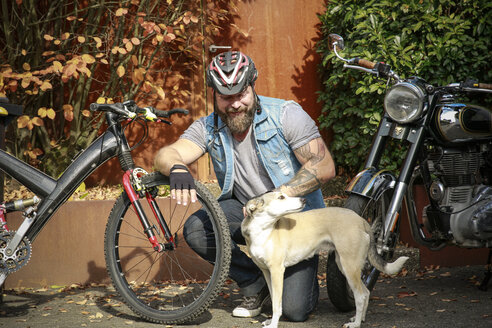 Smiling man with dog between motorbike and bicycle - REAF00419