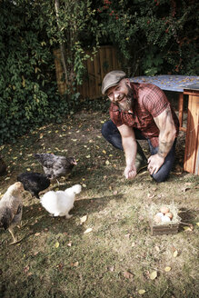 Man in his own garden, man feeding free range chickens - REAF00434