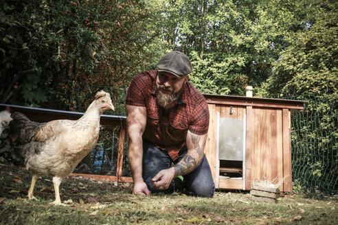 Man in his own garden, man feeding free range chicken - REAF00437