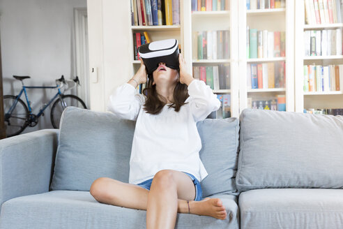 Amazed girl sitting on the couch at home using Virtual Reality Glasses - LVF07516