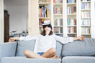 Girl sitting on the couch at home using Virtual Reality Glasses - LVF07519