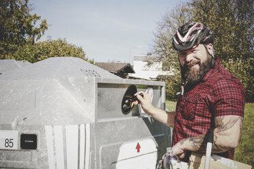 Portrait of man recycling glass bottle in bottle bank - REAF00441