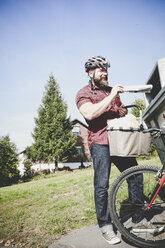 Cyclist recycling waste paper in paper bank - REAF00444