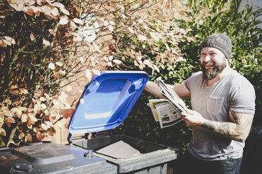 Portrait of laughing man recycling waste paper in paper bank - REAF00450