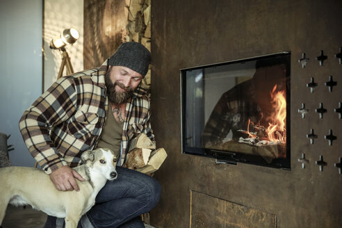Bearded man with his dog in front of fireplace at home - REAF00453
