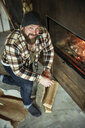 Bearded man with kneeling in front of fireplace at home - REAF00456