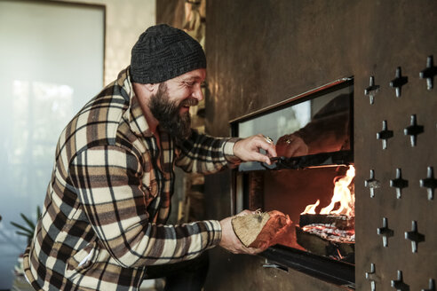 Happy bearded man in front of fireplace at home - REAF00459