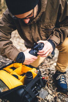 High angle view of hiker adjusting camera while kneeling on field in forest - CAVF52650
