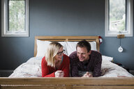 Smiling couple lying on bed at home - CAVF52668