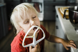 Close-up of girl with eyes closed licking food while standing in kitchen at home - CAVF52677
