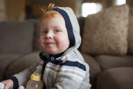 Portrait of cute baby boy with milk bottle wearing warm clothing in living room at home - CAVF52692