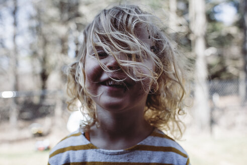 Close-up portrait of happy girl with blond hair standing at yard - CAVF52704