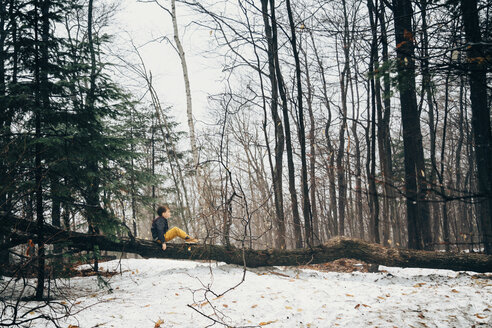 Side view of boy sitting on fallen tree in forest during winter - CAVF52719