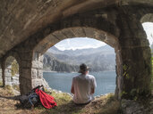 Italy, Hiker sitting under bridge, looking to Lago di Salarno - LAF02139