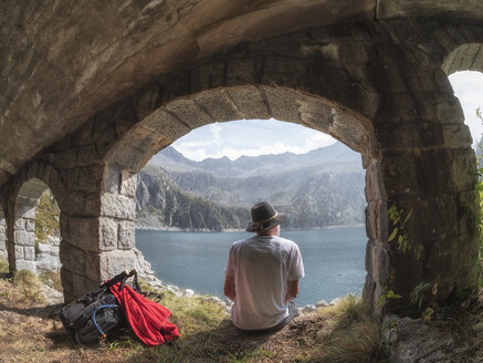 Italy, Hiker sitting under bridge, looking to Lago di Salarno - LAF02139
