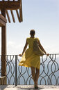 Rear view of young woman looking at sea while standing by railing on balcony - CAVF52760