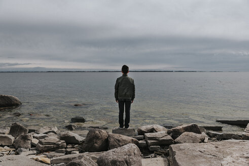 Rear view of boy standing rocks at lakeshore against cloudy sky - CAVF52769